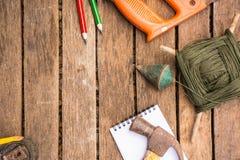 A ferramenta do artesão do fundo tem a serra e o martelo e prumo a prumo e fita métrica e caderno No fundo de madeira Fotos de Stock