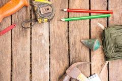 A ferramenta do artesão do fundo tem a serra e o martelo e prumo a prumo e fita métrica e etc. No fundo de madeira Imagens de Stock