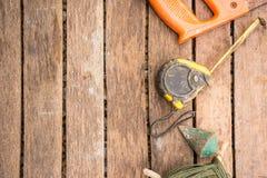 A ferramenta do artesão do fundo tem a serra e prumo a prumo e fita métrica No fundo de madeira Canto direito Imagem de Stock