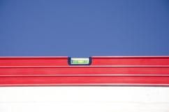 Céu azul da construção exterior vermelha do nível de espírito Foto de Stock Royalty Free