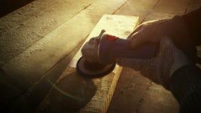 A ferramenta do moedor de ângulo, homem brutal do carpinteiro lustra uma prancha áspera em uma tabela de madeira no por do sol Du vídeos de arquivo