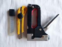 A ferramenta para obras, o stipler da cor preta ao punho branco conecta os suportes do metal dos objetos, uma construção fotografia de stock royalty free