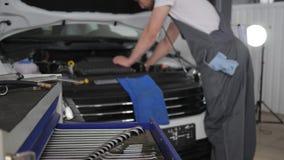 A ferramenta profissional nas mãos mechanician, serviço do carro, mecânico que trabalha na oficina, especialista novo repara carr filme