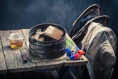Ferramentas antigas do apicultor com favos de mel, chapéus e mel Imagens de Stock Royalty Free