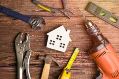 Ferramentas brancas de madeira do brinquedo e da construção da casa no backgrou de madeira fotos de stock