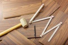 Ferramentas a colocar a estratificação no assoalho de madeira Fotos de Stock