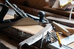 Ferramentas da carpintaria dentro nas placas de madeira em uma oficina pequena foto de stock royalty free
