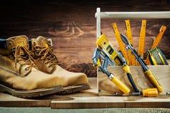 Ferramentas da construção na caixa de ferramentas de madeira e botts de trabalho na madeira do vintage imagem de stock