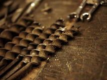 Ferramentas da construção na garagem: Bocados de broca no banco de trabalho de madeira foto de stock