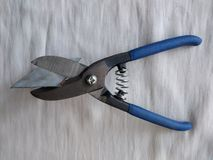 Ferramentas da construção, tesouras pequenas para o corte do metal, um fundo branco imagem de stock