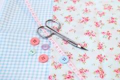 Ferramentas da costura em um fundo floral da tela do vintage com tesouras e botões imagens de stock