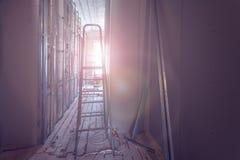 Ferramentas da escada e da construção e interior da sala durante da instalação da placa de gesso ou do drywall para fazer o gypsu fotos de stock