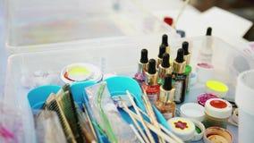 Ferramentas de desenho do close-up com pinturas em uns frascos Arte Grupo incomum de artista com pinturas nos frascos de vidro, e video estoque