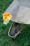 Ferramentas de jardim, carrinho de mão e luvas amarelas Ferramentas de jardinagem novas, bandeja do bastão Trabalhos fora no conc foto de stock royalty free