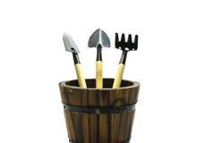 Ferramentas de jardinagem no tambor de madeira no fundo do isolado Fotografia de Stock