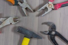 Ferramentas diferentes em um fundo de madeira Alicates, alicates, alicates, martelo Imagem de Stock Royalty Free