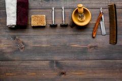 Ferramentas do barbeiro do vintage Lâmina, pente, escova no copyspace de madeira escuro da opinião superior do fundo fotos de stock