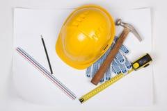 Ferramentas do capacete e do trabalho do construtor amarelo sobre o branco Fotografia de Stock Royalty Free