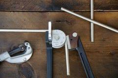 Ferramentas do dobrador do tubo ou do dobrador da tubulação no fundo de madeira Imagens de Stock