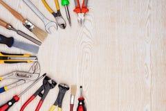 Ferramentas do trabalho na textura de madeira Imagem de Stock