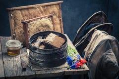 Ferramentas do vintage para a apicultura com favos de mel, chapéus e mel Imagens de Stock Royalty Free