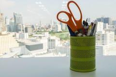 Ferramentas e escritório estacionários na caixa de lápis verde do metal na mesa de escritório Imagem de Stock