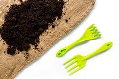 ferramentas e terra verdes de jardim para plantar flores na opinião superior do fundo branco da tabela Fotografia de Stock Royalty Free