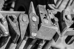 Ferramentas históricas de um ferreiro em um mercado medieval tal como o martelo, formão, espeto, formão, placa batendo, pilão, ma foto de stock
