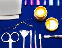 Ferramentas para o tratamento de mãos, amarelo da cor do prego do gel, contramestre desarrumado da vertente na tabela azul resist Fotos de Stock