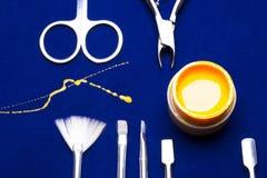 Ferramentas para o tratamento de mãos, amarelo da cor do prego do gel, contramestre desarrumado da vertente na tabela azul resist Foto de Stock Royalty Free