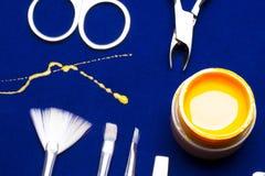 Ferramentas para o tratamento de mãos, amarelo da cor do prego do gel, contramestre desarrumado da vertente na tabela azul resist Imagens de Stock Royalty Free