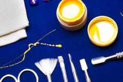Ferramentas para o tratamento de mãos, amarelo da cor do prego do gel, contramestre desarrumado da vertente na tabela azul resist Foto de Stock