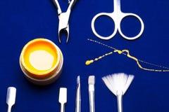 Ferramentas para o tratamento de mãos, amarelo da cor do prego do gel, contramestre desarrumado da vertente na tabela azul resist Imagem de Stock Royalty Free