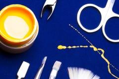 Ferramentas para o tratamento de mãos, amarelo da cor do prego do gel, contramestre desarrumado da vertente na tabela azul resist Fotografia de Stock Royalty Free