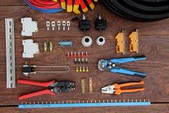 Ferramentas para os trabalhos de eletricidade apresentados em uma superfície de madeira do marrom Vista superior fotografia de stock royalty free