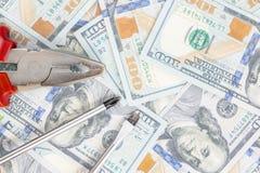 Ferramentas que encontram-se sobre 100 dólares de fundo das cédulas Alicates e chave de fenda contra o dinheiro dos E.U. Correção Fotografia de Stock