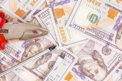 Ferramentas que encontram-se sobre 100 dólares de fundo das cédulas Alicates e chave de fenda contra o dinheiro dos E.U. Correção foto de stock royalty free