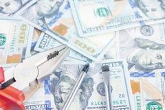 Ferramentas que encontram-se sobre 100 dólares de fundo das cédulas Alicates e chave de fenda contra o dinheiro dos E.U. Correção Fotografia de Stock Royalty Free