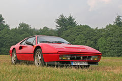 Ferrari 328 in the grass. Ferrari 328 GTB standing in the grass with trees in the background Royalty Free Stock Photo