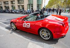 Ferrari California luxury coupe sports car rental along the Champs-Elysee. Travel and tourism royalty free stock image