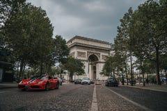 Ferrari, das durch Arc de Triomphe Paris, Frankreich fährt stockfotografie