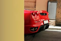 April 3, 2016, Kiev, Ukraine. Ferrari F430. Red supercar. Abstract photo. Luxury car peeking out from behind the wall royalty free stock image