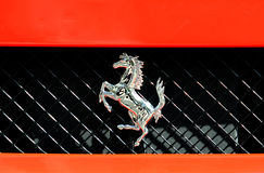 Ferrari Logo. Shiny horse logo on a red Ferrari Royalty Free Stock Image