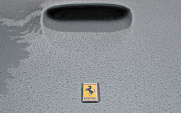 Ferrari logo on rainy bonnet. 254415844,0Ferrari logo on a rainy bonnet with an air inlet in the background. Logo in focus, blurred to the back Stock Photos