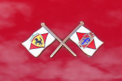 Ferrari- and Pininfarina Flags Crossed Badge. On `roso` red Royalty Free Stock Images