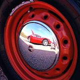 Ferrari reflected in hubcap. Stock Photo