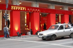 Ferrari Store - Bucharest. Saturday, December 5, 2009. A romanian car passes in front of a new Ferrari Store, opened saturday, downtown Bucharest, Romania royalty free stock photos