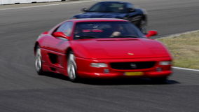 Ferrari Track Day. Various Ferrari sports cars driving on track during the Italia a Zandvoort event at the Zandvoort race track. The cars are two F355, 599 GTB stock video footage