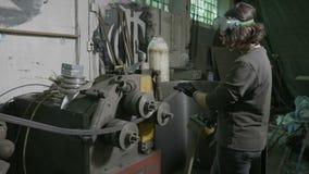 Ferreiro da mulher que dobra uma barra de ferro usando uma máquina de dobra profissional do metal em sua própria oficina - video estoque
