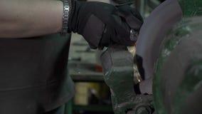 Ferreiro da mulher que lustra uma cabeça do parafuso do metal usando uma máquina de moedura que faça sparkles em uma oficina no m filme